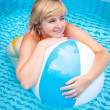 Happy attractive woman with beach ball in swimming pool — Stock Photo #13276761
