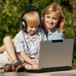 The little boy and mother with the laptop in park — Stock Photo #13276779