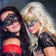 Happy young girls under masks on the party — Stock Photo