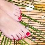 Beautiful feet leg with perfect spa pedicure on bamboo — Stock Photo