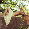 Beautiful nude woman lies on stones against nature background - Stock Photo