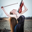 The red-haired girl with a violin outdoor — Stock Photo #13276969
