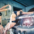 Stock Photo: Models at car wash in garage. Cross processing