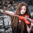 The red-haired girl with a violin sitting on the ashes — Stock Photo #13277022