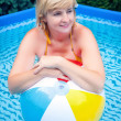Happy attractive woman with beach ball in swimming pool - Lizenzfreies Foto