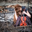 The red-haired girl with a violin sitting on ashes — Stock Photo