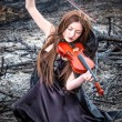 The red-haired girl with a violin sitting on the ashes — Stock Photo #13277165