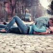 Couple of teenagers lying in street together — Stock Photo