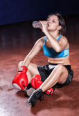 The girl boxer sitting on a floor in a hall after tiresome train — Stock Photo