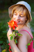 Woman doing garden work sniffing at the rose — Stock Photo