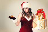 Beautiful woman in a red dress and hat of Santa with a big gift — Foto Stock