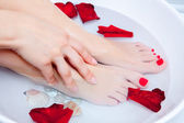 Woman spa pedicure foot treatment with water and flower — Stock Photo
