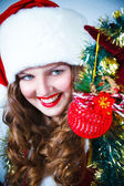 Beautiful woman in a red dress and hat of Santa with a christmas — Foto Stock
