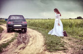 The thrown bride on the rural road with an old suitcase — Stock Photo