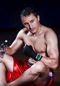 The boxer sitting on a floor in a hall after tiresome training — Stock Photo
