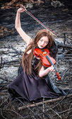 The red-haired girl with a violin sitting on the ashes — Stok fotoğraf