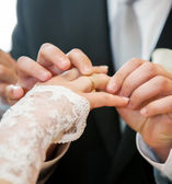 Mans hand putting a wedding ring on the brides finger — Photo