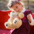 Small beautiful girl and amusing bear - Stock Photo