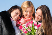 Three women with tulips — Stock Photo