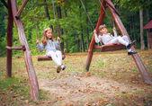 Girlfriends on swing in park — Stock Photo