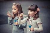 Little girls blowing  bubbles — Stock Photo
