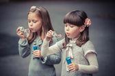 Little girls blowing  bubbles — Stockfoto