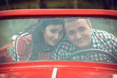 Young couple in a retro car — Stock Photo