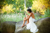 Woman sitting on  stone — Stock Photo