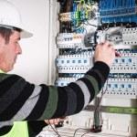 Electrician checking a fuse box — Stock Photo #37179919