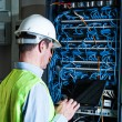 Electrician checking a fuse box — Stock Photo #37179947