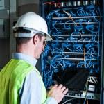 Electrician checking a fuse box — Stock Photo #37179947