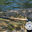Stock Photo: Flyfishing rod on the stone by the river