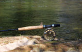 Flyfishing rod on the stone by the river — Stock Photo