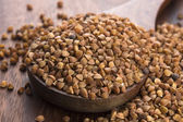 Buckwheat seeds on wooden spoon in closeup — Stock Photo