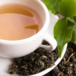Cup of green tea with freh leaves — Stock Photo