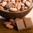 Cacao beans with milk chocolate — Stock Photo