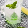 Glass made of ice with vodka, lemon and mint — Stock Photo #48958381