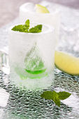 Glass made of ice with vodka, lemon and mint — Stock Photo
