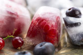 Fresh berry fruits frozen in ice cubes — Foto Stock