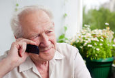 задумчивый старший мужчина с телефоном — Стоковое фото