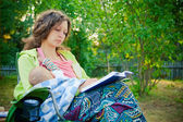 Mother breastfeeding while reading the book — Stock Photo