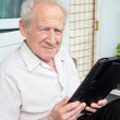 Senior man holding a touchpad PC in his hands — Stock Photo #45016143