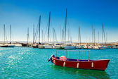 Small red boat in front of the yachts — Stock Photo