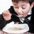 Stock Photo: The boy eats the soup with meatballs
