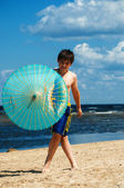 Boy with umbrella on the beach — Stock Photo