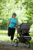 Young woman with a stroller — Stock Photo