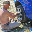 Senior man changing a wheel of his car — Stock Photo #11949220