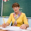 Stock Photo: Teacher seating in front of blackboard