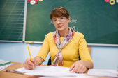 Teacher seating in front of blackboard — Stock Photo