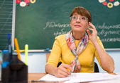 Teacher seating in front of blackboard — Stockfoto